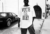 Opa-Locka, Miami-Dade County, Florida.USA.November 2, 2004..Voters line up with observers and lawyers from both sides watching over the voters and pollsters...A voters wears the tee shirt with the rapers P.Diddy sloggen..