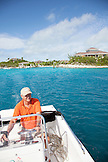 EXUMA, Bahamas. Yves, a manager at the Fowl Cay Resort driving the resort speedboat with the Fowl Cay Resort in the background.