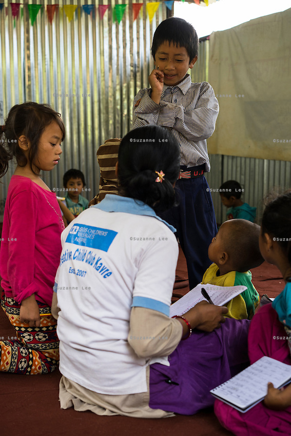 Aakash Tamang, 9, shows his notebook to the teacher in the SOS Children's Villages Child Care Space in Rayale, Nepal on 1 July 2015. Aakash Tamang's house had collapsed during the earthquake on 25th April 2015. Fortunately, all his family members are safe, but they are now displaced. Aakash has been very fond of the Child Care Space, where he enjoys learning, doing drama plays, and dancing with his friends. Photo by Suzanne Lee for SOS Children's Villages