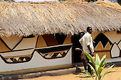Kasanga, Tanzania. Man outside thatched house with traditional geometric graphic design painted on the outside walls.
