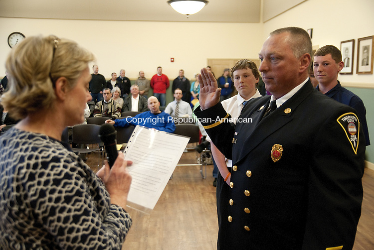 TORRINGTON, CT, 01 APRIL 15 -  Torrington Fire Capt. Kevin Engle is sworn in to his new rank Wednesday by Mayor Elinor C. Carbone during a Board of Public Safety meeting at City Hall as his sons Cole and Kyle look on. Engle was promoted to Captain last month.    Alec Johnson/ Republican-American