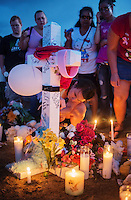 Rachael Vijil (cq), 25, the cousin of Micayla Medek, 23, who was one of the 12 victims of the mass shooting, lights a candle at a shrine built near the Aurora Century 16 movie theater in Aurora, Colorado, Sunday, July 22, 2012. Suspect James Holmes, allegedly went on a shooting spree and killed 12 people and injured 59 during an early morning screening of 'The Dark Knight Rises.'..Photo by MATT NAGER
