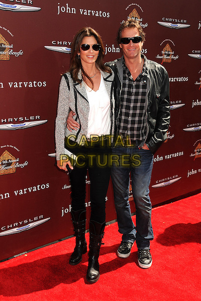 Cindy Crawford, Rande Gerber.9th Annual Stuart House Benefit held at John Varvatos Los Angeles, USA..11th March 2012.full length white jacket grey gray shirt sunglasses shades jeans denim check shirt boots leather married husband wife  .CAP/ADM/BP.©Byron Purvis/AdMedia/Capital Pictures.