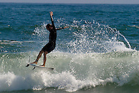 A surfer jumps off of a wave at Rockaway Beach, NY.