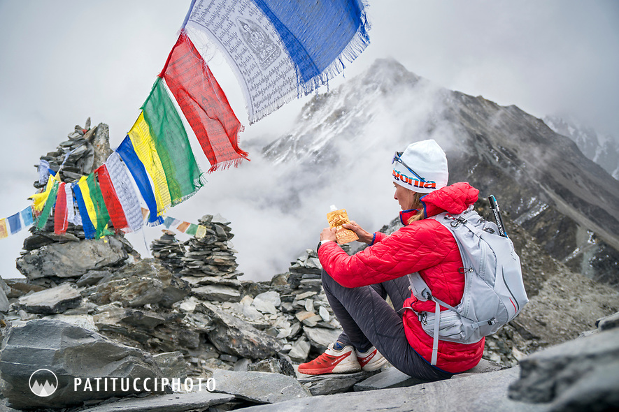 A trail runner sits eating on top of Chukhung Ri, a 5546 meter highpoint above Chukhung, in the Khumbu Region of Nepal.