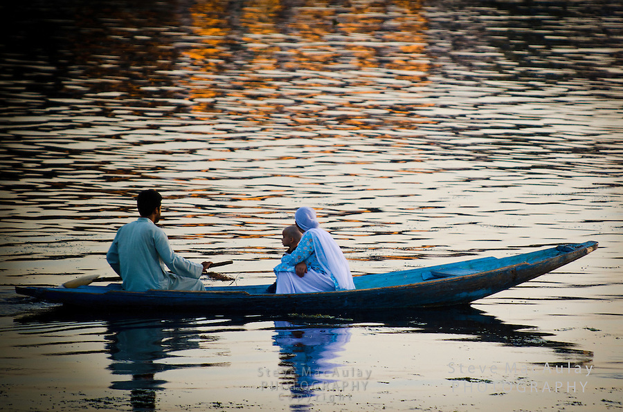 Muslim family on a Shikara, or gondola boat, on Dal Lake, Srinagar, Kashmir, India.