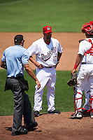 Auburn Doubledays pitching coach Tim Redding (17) talks with starting pitcher McKenzie Mills (hidden) and catcher Luis Vilorio (4) as umpire Dane Ponczak breaks up the mound meeting during a game against the Vermont Lake Monsters on July 13, 2016 at Falcon Park in Auburn, New York.  Auburn defeated Vermont 8-4.  (Mike Janes/Four Seam Images)