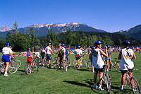 Whistler Resort, BC, British Columbia, Canada - Cyclists and Bicycles in Rainbow Park at Alta Lake, Summer - Blackcomb Mountain Ski Runs in distance