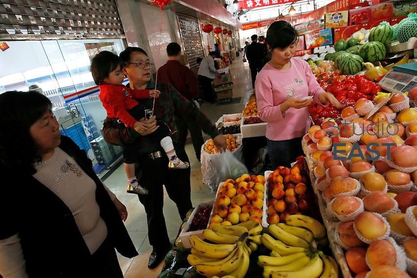 Gao Cuilan (left) and Li Fang (third from left), carying his grand-daughter Li Siqi (second from left), shop at the vegetables market in Baoshan, near Shanghai, on May 7, 2008. Photo by Lucas Schifres/Pictobank..Gao Cuilan (gauche) et Li Fang (troisième en partant de la gauche), qui porte sa petite-fille Li Siqi (deuxième en partant de la gauche) font des courses de fruits au marché à Baoshan, près de Shanghai, le 7 mai 2008. Gao Cuilan marchande tout pour récupérer quelques centimes. « La viande de porc et les légumes ont beaucoup augmenté, explique-t-elle. Quand on est arrivés à Shanghai, on payait 4 mao (3 centimes d'euros) une livre de pommes de terre. Maintenant, c'est 2,8 RMB ( 25 centimes d'euros). » En février, les prix des biens de consommation ont encore augmenté de 8,7%. Photo par Lucas Schifres/Pictobank