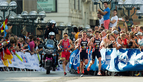 12 JUL 2014 - HAMBURG, GER - Jonathan Brownlee (GBR) from Great Britain leads the front pack of his brother Alistair Brownlee (GBR) (2nd from right), Vincent Luis (hidden) of France and series leader Javier Gomez (ESP) (left) from Spain during the run at the elite men's 2014 ITU World Triathlon Series round in the Altstadt Quarter, Hamburg, Germany (PHOTO COPYRIGHT © 2014 NIGEL FARROW, ALL RIGHTS RESERVED)