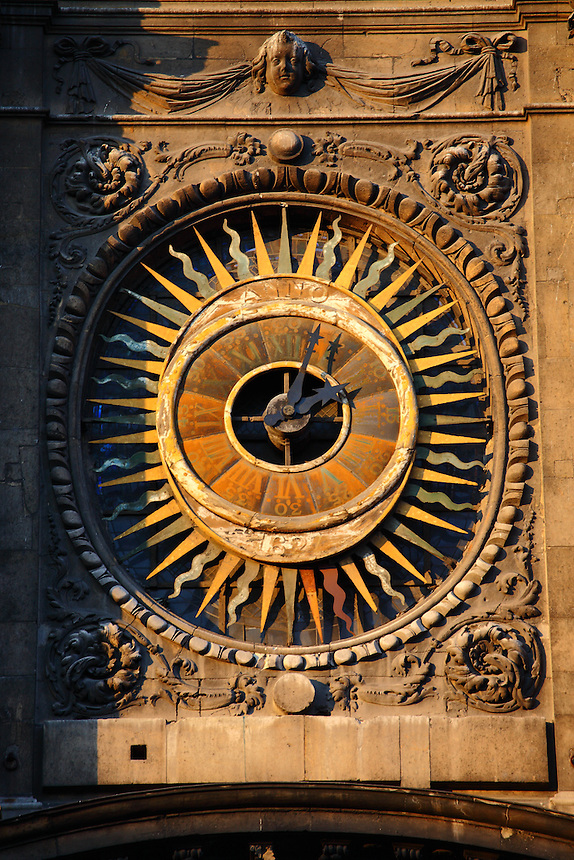 The enlightened ancient clock on the front of the Saint Paul and Saint Louis church of the Marais in Paris. Digitally Improved Photo.