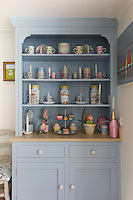 A pale blue dresser displays a colourful collection of jars and candle holders