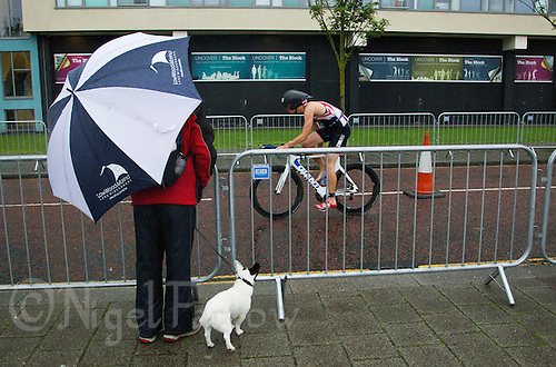 10 AUG 2014 - LIVERPOOL, GBR - A spectator watches a competitor starting his bike leg during the Tri Liverpool triathlon which incorporated the 2014 British Age Group Triathlon Championships in Kings Dock in Liverpool, Great Britain (PHOTO COPYRIGHT © 2014 NIGEL FARROW, ALL RIGHTS RESERVED)