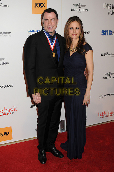 "John Travolta, Kelly Preston .10th Annual ""Living Legends of Aviation"" Awards held at the Beverly Hilton Hotel, Beverly Hills, California, USA, .18 January 2013..Full length navy blue ruched dress long maxi medal suit husband wife couple black shirt .CAP/ADM/BP.©Byron Purvis/AdMedia/Capital Pictures."
