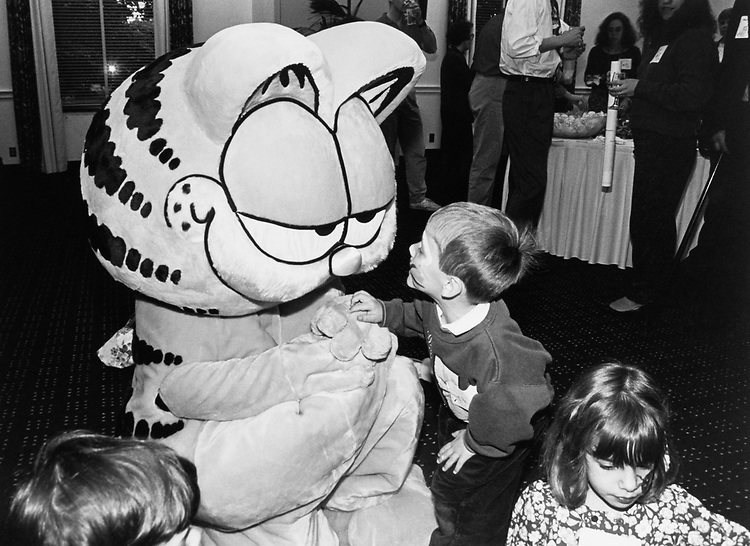 """Garfield""cartoonist Jim Davis present with lots of kids. Brett Miller, (age 4, son of Rep. John Miller, R-Wash.) shows Garfield his painted face. Hana (age 4, daughter of Sen. Joe Lieberman, D-Conn.) is in the foreground at a eception in Rayburn sponsored by the National Wildlife Federation on May 11, 1992. (Photo by Laura Patterson/CQ Roll Call)"