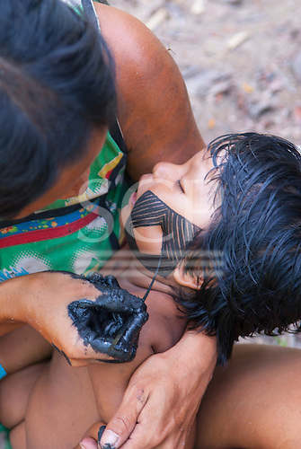 Aldeia Baú, Para State, Brazil. Kayapo woman painting an intricate design on the cheek of her son.