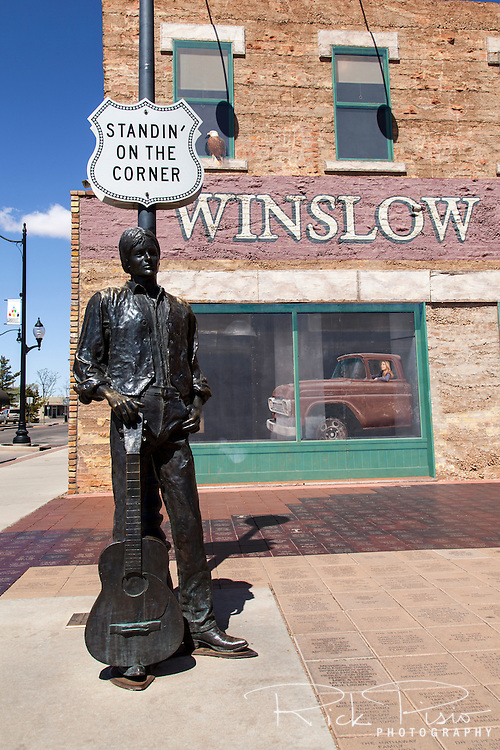 After Interstate 40 bypassed Winslow in the late 1970's, and Route 66 was removed from the maps, Winslow had seen a steady decline. In 1997, after their success in restoring the historic La Posada Hotel, business leaders gathered together to design and build a park in downtown Winslow that paid tribute to the Jackson Browne &amp; Glenn Frey lyrics in the song &quot;Take it Easy&quot; and it was decided to build a park in Winslow's downtown area. <br /> <br /> The Standin' On the Corner Foundation sent out requests for proposals to dozen of architects and settled on a design that included a mural and bronze statue depicting a 1970's man standing on the corner wearing jeans, boots, shirt and vest with a guitar standing on the toe of his boot. The park also had planters with built-in seating, native landscaping trees, lighting, and inscribed bricks. After two years of dedicated effort the dedication celebration took place on September 10 &amp; 11, 1999.