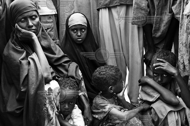 30 year old Fatima Aden Mohammed from Bardera in the Juba valley, Somalia protects her four year old daughter Dahira (2nd from left), who has malaria outside the registration camp at the Dagahaley camp part of the Dadaab refugee camp in Kenya. Her other daughter, two year old Habiba, died on the way to the camp. The drought is the worst in East Africa for 60 years. The UN described it as a humanitarian emergency. The already overcrowded complex received 1,000 new refugees a day in June, five times more than a year ago. About 30,000 people arrived at the Dadaab refugee camp in June, according to UNHCR compared to 6,000 in June 2010.