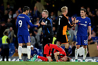 Huddersfield Town's Assistant Head Coach, Christoph Buhler shakes hands with Chelsea's Alvaro Morata and goalkeeper, Jonas Lossl shakes hands with Andreas Christensen as Florent Hadergjonaj emotionally puts his head against the Stamford Bridge grass during Chelsea vs Huddersfield Town, Premier League Football at Stamford Bridge on 9th May 2018