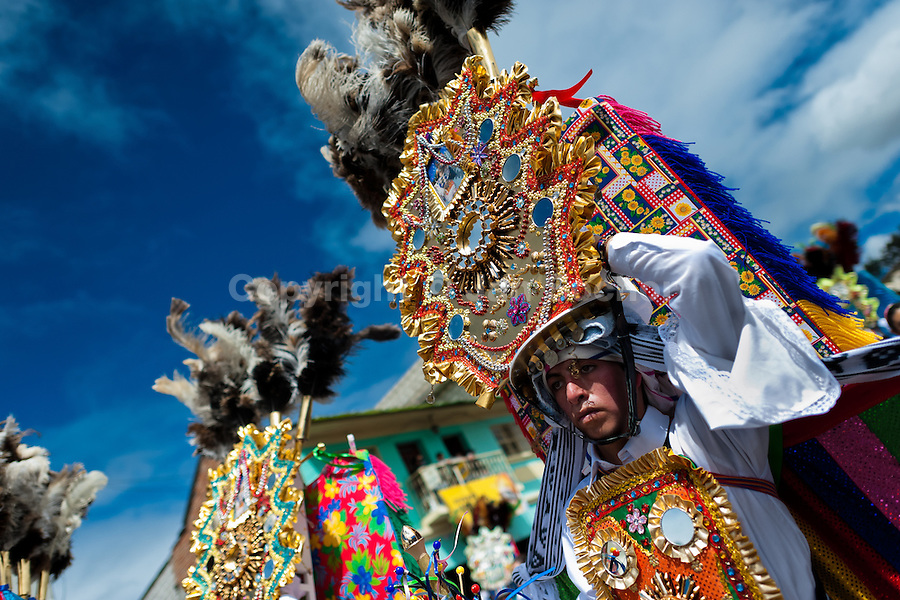A young dancer (danzante) takes part in the religious parade within the Corpus Christi festival in Pujilí, Ecuador, 10 June 2012. Every year in June, thousands of people gather in a small town of Pujili, high in the Andes, to celebrate the Catholic feast of Corpus Christi. Introduced originally during the Spanish conquest of South America, this celebration merges Catholic rituals of Holy Communion with the traditional Andean harvest and sun festivities (Inti, the Inca sun god). Women dancers perform wearing brightly colored costumes while men dancers wear chest ornaments and heavy elaborate headdresses adorned with mirrors, jewelry, or natural items (shells). Being a dancer in the Corpus Christi ceremonial parade (El Danzante) is considered an honour and a privilege by the indigenous people in Ecuador.