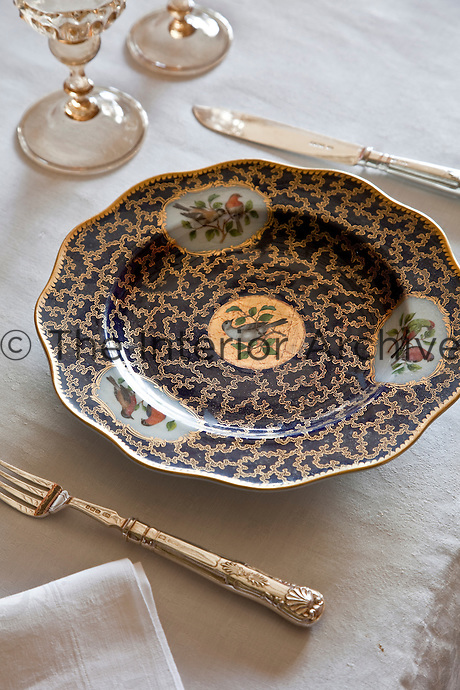 One of the place settings on the dining table with an antique dish decorated with birds