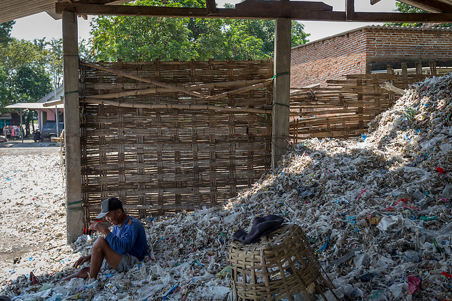 21 May 2019, Bangun Village,East Java, Indonesia: Local man Giman, a rag picker speaks about Australian branded waste in dumps at Bangun Village outside Surabaya, Indonesia. Millions of tonnes of recyclable plastic trash from Australia and Europe is dumped for rag pickers to separate and sort. The plastics are used to fuel fires at local tofu factories among other industries. Australia is illegally sending non recyclable trash hidden within this lode and the Indonesian Government is cracking down on the practice and preparing to refuse to take Australia's rubbish that is creating environmental and health issues locally. Picture by Graham Crouch/The Australian