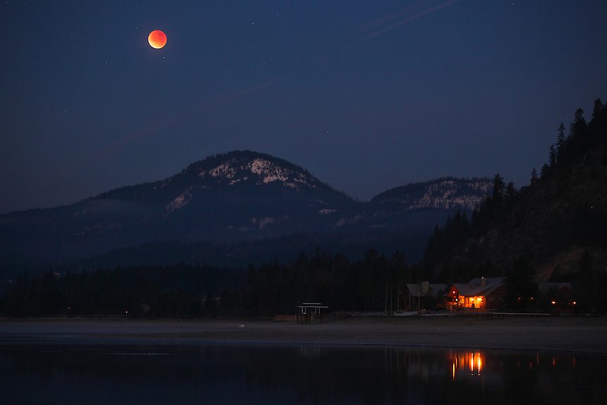 A lunar eclipse moon begins to set behind the Selkirk Mountain Range on Lake Pend Oreille near Sandpoint, Idaho on December 10, 2011.
