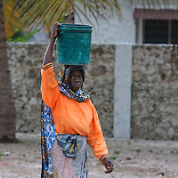 Jambiani, Zanzibar, Tanzania.  Woman Carrying Water Home, Early Morning.
