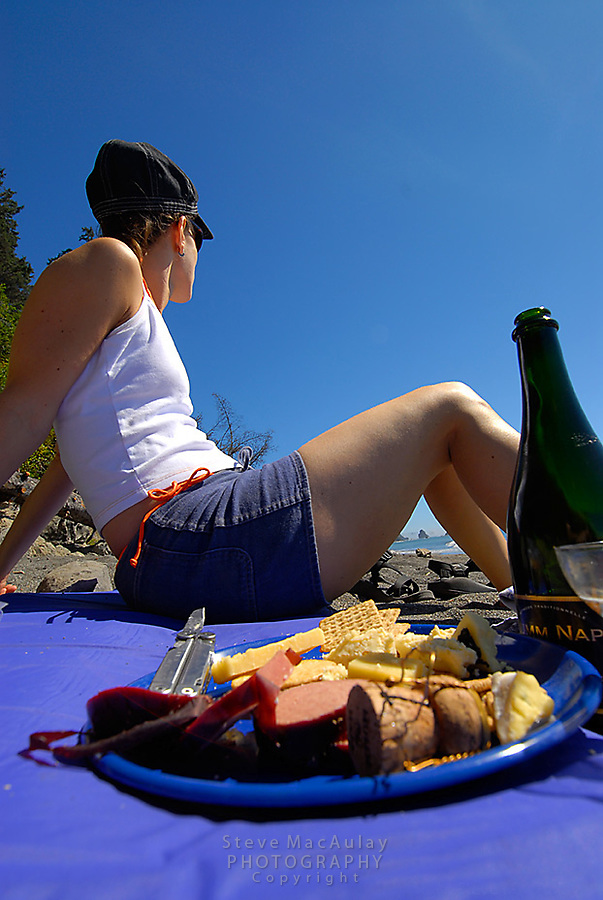 Woman relaxing on camping pad with plate of cheese and crackers and champagne, Third Beach, Olympic National Park, Coastal Strip, Olympic National Park, WA.