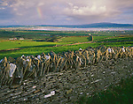 County Clare, Ireland<br /> Rainbow and clearing storm clouds over stone fences and green hillsides near the village of Lahinch on Liscannor Bay
