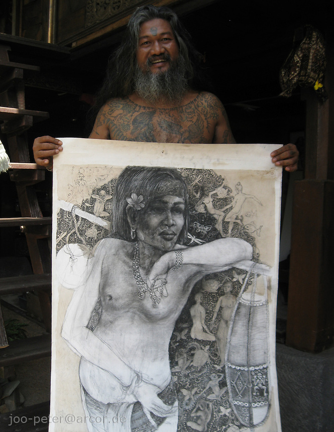 painter Kan Kulak shows pencil drawing in his atlier, Ubud,  Bali, archipelago Indonesia