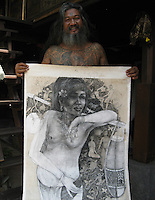painter Kan Kulak shows pencil drawing in his atlier, Ubud,  Bali, archipelago Indonesia