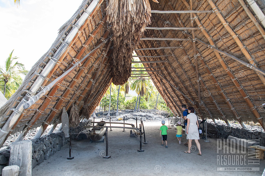 A family explores a traditional thatched hale (house or structure) an a display of traditional implements and more at Pu'uhonua o Honaunau, Big Island.