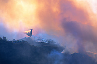 870000343 a los angeles county fire fighting helicopter performs aerial retardant drop on homes directly in the burn path of the topanga fire in the hills above the san fernando valley in southern california