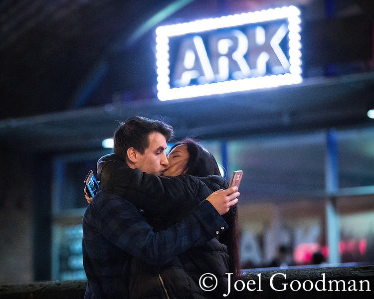 "© Joel Goodman - 07973 332324 . 17/12/2016 . Manchester , UK . A couple embrace and kiss whilst operating their mobile phones at Deansgate Locks . Revellers out in Manchester City Centre overnight during "" Mad Friday "" , named for being one of the busiest nights of the year for the emergency services in the UK . Photo credit : Joel Goodman"