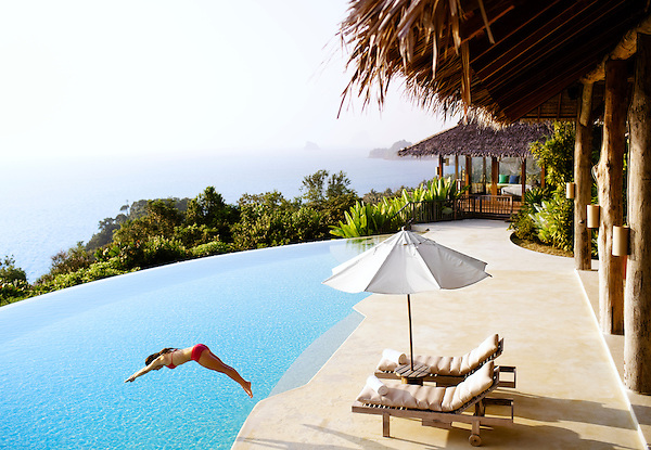 A woman dives into the infinity pool of the Hilltop Reserve, a three-bedroom private pool villa overlooking Phang Nga Bay at Six Senses Hideaway Yao Noi. Thailand.