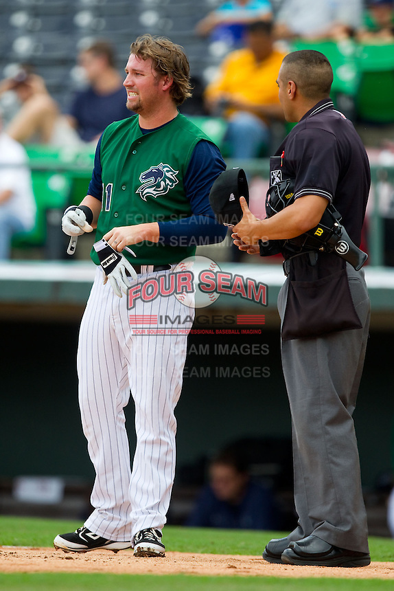 Andy Wilkins (11) of the Charlotte Knights discusses a called third strike with home plate umpire Gabe Morales during the International League game against the Durham Bulls at Knights Stadium on August 18, 2013 in Fort Mill, South Carolina.  The Bulls defeated the Knights 8-5 in Game One of a double-header.  (Brian Westerholt/Four Seam Images)