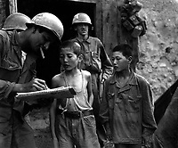 Two North Korean boys, serving in the North Korean Army, taken prisoner in the Sindang-dong area by elements of the 389th Inf. Regt., are interrogated by a U.S. soldier shortly after their capture.  September 18, 1950. Pfc. Francis Mullin. (Army)<br /> NARA FILE #:  111-SC-348805<br /> WAR & CONFLICT BOOK #:  1494
