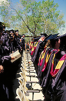 rows of students in caps and gowns at college graduation ceremony. students, graduates.