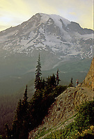 A solitary hiker stands on an exposed trail watching sunset light change on 14,410 feet high Mount Rainier.  Mount Rainier National Park, Washington State.....Photographed in 35mm format on Velvia 50 film.