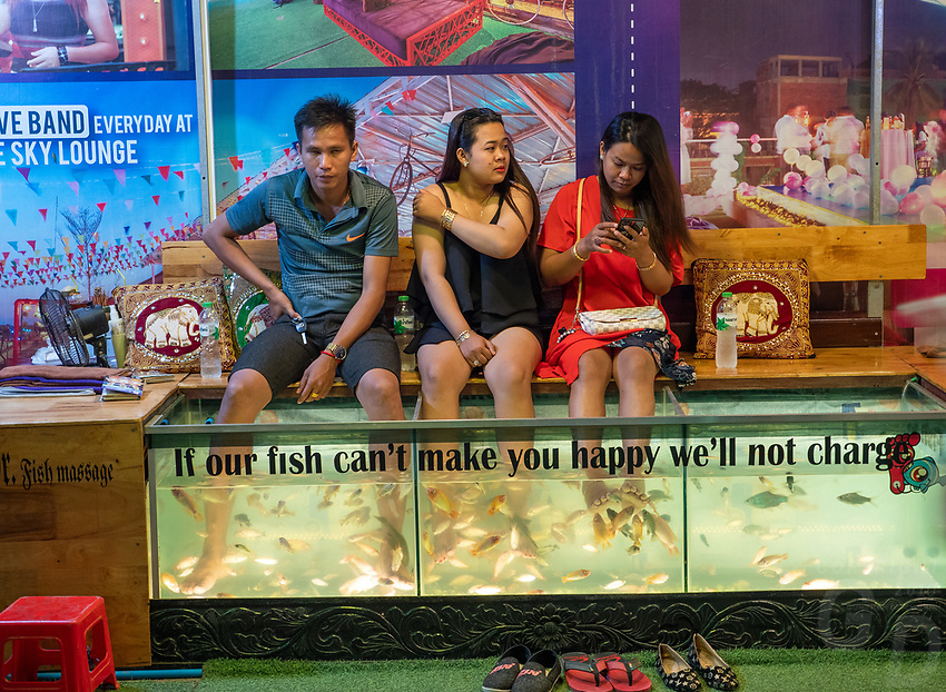 Night scene in Pub street, Siem Reap, Tourists getting their feed cleaned by fish while hanging their feet in a fish tank. Cambodia.