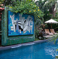 View of swimming pool and decked area including a large rendered and copper patinated wall with a  tiled panel by Brazilian landscape designer, Roberto Burle Marx