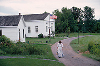 Woman in period costume walks up the village path in Erie Canal Village, a recreated nineteenth century town, in Rome, New York. American history, landmarks. Rome New York, Erie Canal Village.