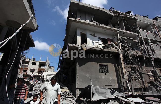 Palestinians inspect the remains of their houses, which witnesses said was hit by an Israeli air strike in Jabalia refugee camp in the northern Gaza Strip on August 9, 2014. Israel launched more than 20 aerial attacks in Gaza early on Saturday and militants fired several rockets at Israel in a second day of violence since a failure to extend an Egyptian-mediated truce that halted a monthlong war earlier this week. The Israeli military said that since midnight it had attacked more than 20 sites in the coastal enclave where Hamas Islamists are dominant, without specifying the targets. Medical officials in Gaza said two Palestinians were killed when their motorcycle was bombed and the bodies of three others were found beneath the rubble of one of three bombed mosques. The air strikes which lasted through the night also bombed three houses, and fighter planes also strafed open areas, medical officials said. Photo by Ashraf Amra