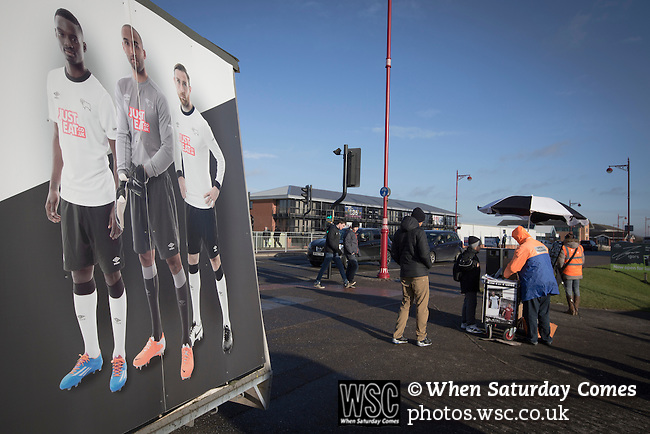 Derby County 1 Nottingham Forest 2, 17/01/2015. iPro Stadium, Championship. Fans walking past an advertising hoarding outside the iPro Stadium, pictured before Derby Country's Championship match against Nottingham Forest. The match was won by the visitors by 2 goals to 1, watched by a derby-day crowd of 32,705. The stadium, opened in 1997, was formerly known as Pride Park. Photo by Colin McPherson.