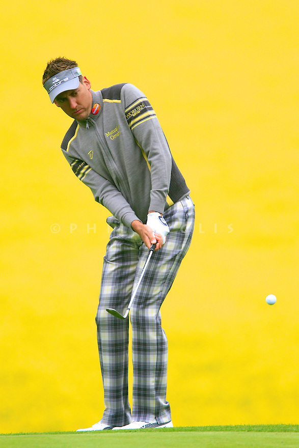 Ian Poulter plays a chip to the 7th green on the Marquess Course at Woburn Golf Club against a blazing backdrop of an adjacent oilseed rape field ( Picture Credit / Phil Inglis )