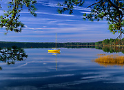 Reflection of yellow sailboat in Lake Massabesic in Auburn, New Hampshire USA.