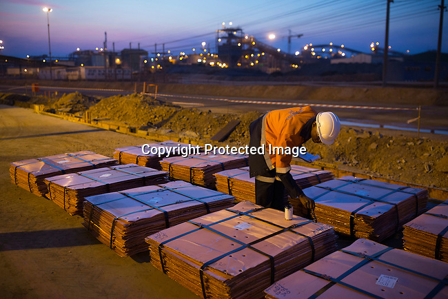 KOLWEZI, DRC- JULY 7: A worker inspects batches of processed copper at Mutanda Mining Sarl, owned (69%) by Glencore, an Anglo-Swiss multinational commodity trading and mining company on July 7, 2016 in Kolwezi, DRC. These copper sheets are ready for shipping by truck to ports such as Dar es Salaam, Tanzania or Durban, South Africa. The mine is mainly producing copper but also some cobalt. The mine employs about 3,500 people and its located in Luabala Province in Southern DRC. (Photo by Per-Anders Pettersson)
