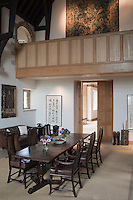 The spotlit tapestry hanging in the gallery becomes a focal point in the double-height dining room