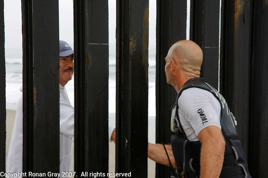 "Tom Jones shakes hands with a man on the other side of the US ? Mexico border at Border Field State Park, the south-western most corner of the contiguous United States, Fiday, November 9 2007.  Jones became the first person to paddle the entire 1250-mile coast of the California on a paddleboard when his three and a half month long journey ended at the border fence in southern San Diego.   The expedition, called ""California Paddle 2007? was designed to draw attention to the problem of plastic pollution in the world?s oceans and its detrimental effect on marine life.  (Photo Ronan Gray)"